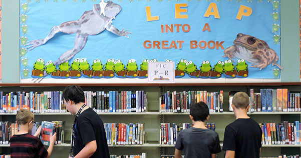 students look for books in the school media center