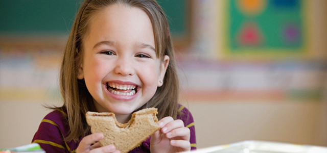 a young girl smiles as she takes a bite from a sandwich