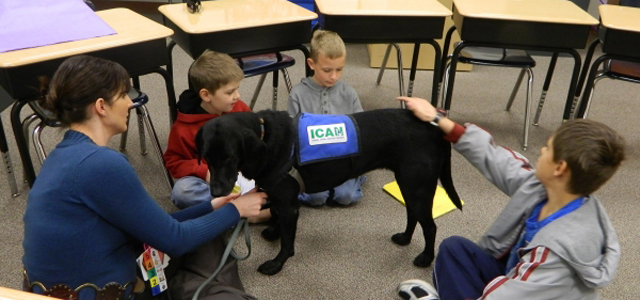 a district service dog visits with students