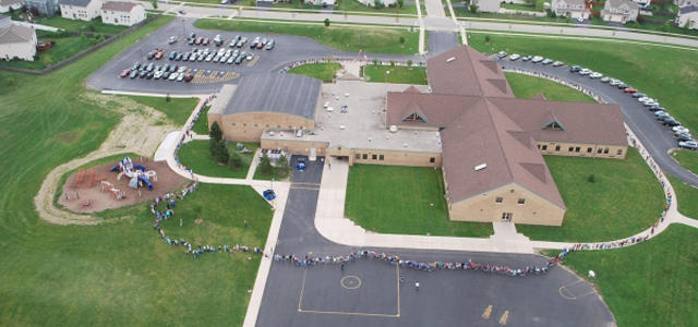 Students and staff at Lincoln Elementary School celebrate diversity by participating in a giant school hug